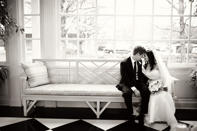 black and white photo of bride and groom sitting on long cushioned bench next to window panes