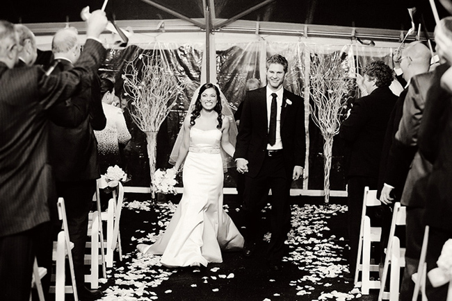 black and white photo of couple walking down aisle at recesional