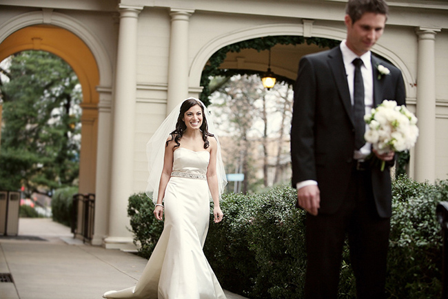 bride in white and veil has first look with groom dressed in black tuxedo and black tie