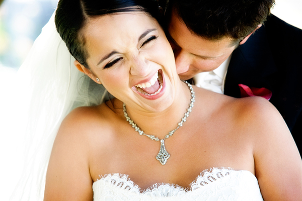 laughing bride and groom kissing her neck