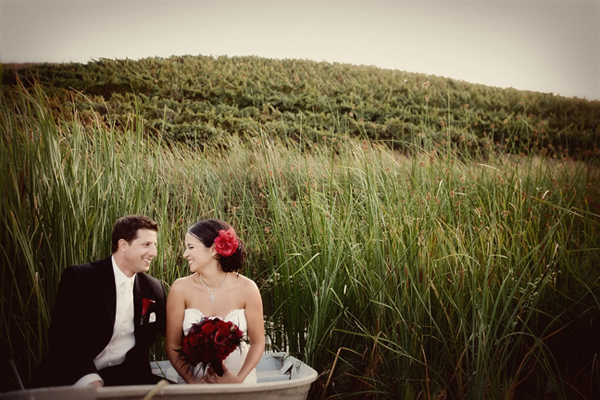 newlyweds sit in boat among tall grass