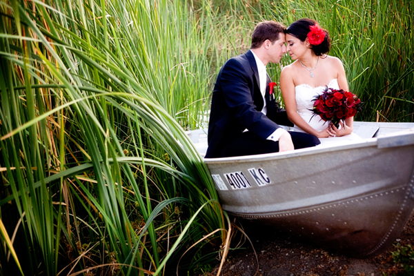 newlyweds sitting in boat among tall grass