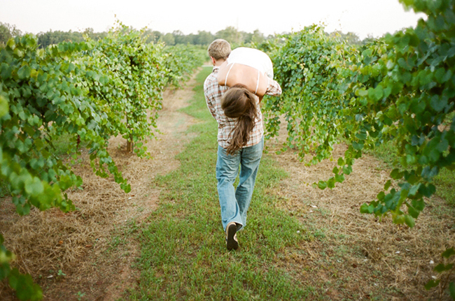 Engagement shoot with groom-to-be carrying bride-to-be over shoulder in vineyard