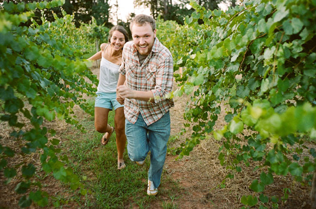 Engaged couple holding hands and running through vinyard for engagement