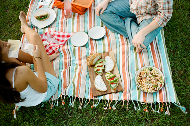 Engaged couple having a picnic on a striped picnic blanket in a vinyard with bread and avocado during A Grape Vineyard Picnic Engagement Shoot