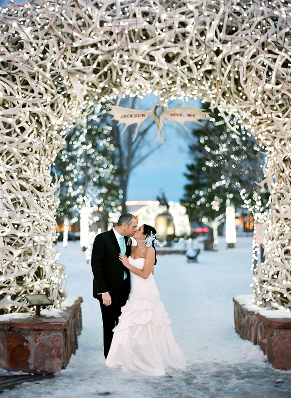 Bride and Groom kiss outside under antlers for a winter wedding in Jackson Hole
