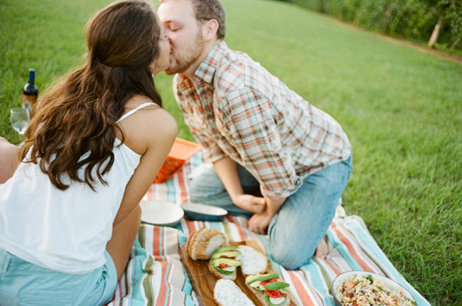 Engaged couple kissing and having a picnic on a striped picnic blanket in a vinyard with bread and avocado and wine