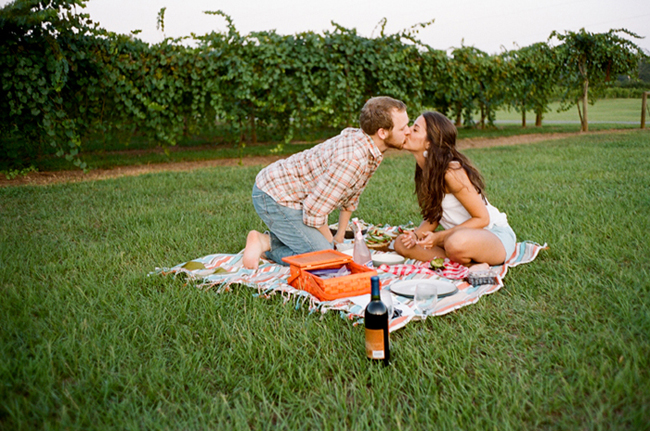 Engaged couple kissing and having a picnic on a striped picnic blanket in a vinyard with bread, avocado, and wine with grape vines in the back ground