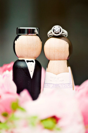 Black wedding band and round diamond engagement ring with halo on bride and groom cake topper