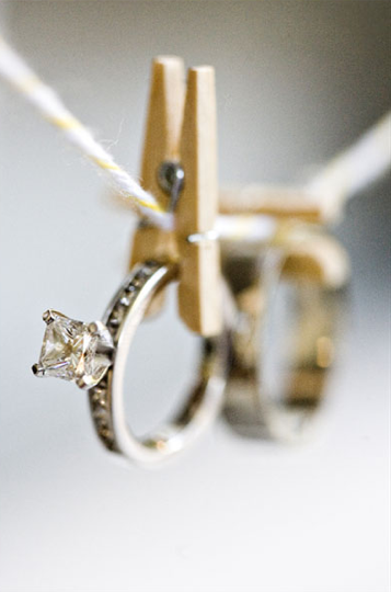 Princess cut engagement ring with side diamonds hung from clothes peg and twine