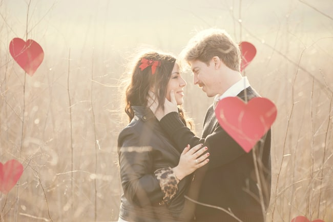 couple in field with red paper hearts