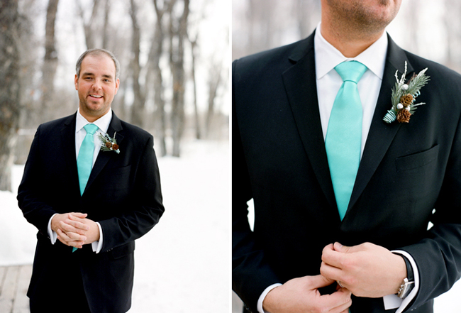 Groom in the snow with aqua blue necktie and black tuxedo