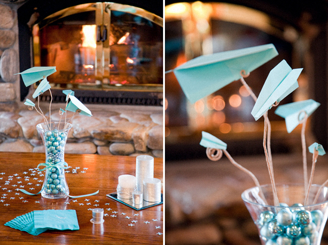 aqua blue paper airplanes and napkins in front of fireplace