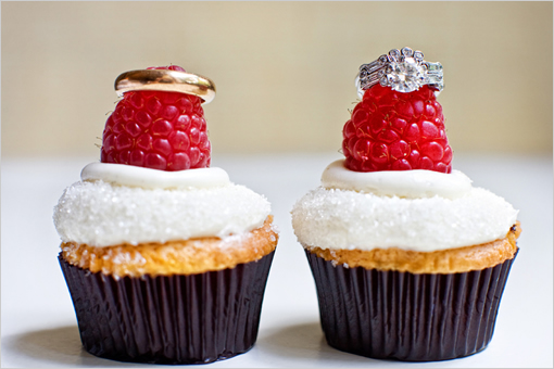 Gold Wedding band and white gold round diamond engagement ring on a raspberry on a vanilla cupcake with white icing in Unique Ring Shots!