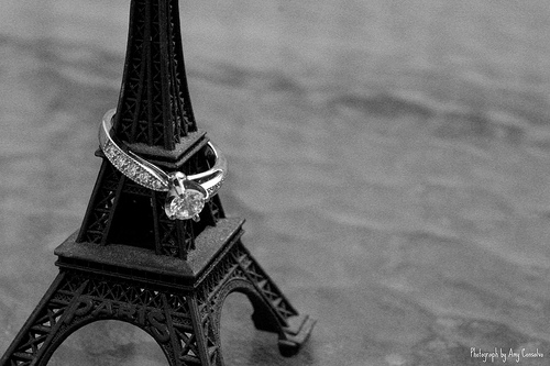 Round diamond engagement ring with small diamond on band on top of black eifel tower