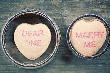 """Photo of wedding bands with sweet hearts inside the rings. sweet hearts say """"dear one"""" and """"marry me"""""""
