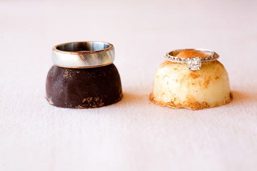 White gold wedding band and white gold engagement ring with a round diamond sitting on top of chocolate