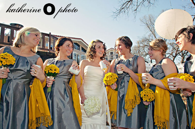 Bridemaids wearing grey dresses with yellow pashmina and holding white coffee mugs and yellow bouquet of mums. Bride in white strapless gown holding a bouquet of white hydrangeas and a white coffee mug. White lantern hanging from tree in Yellow and Grey Backyard Fall Wedding