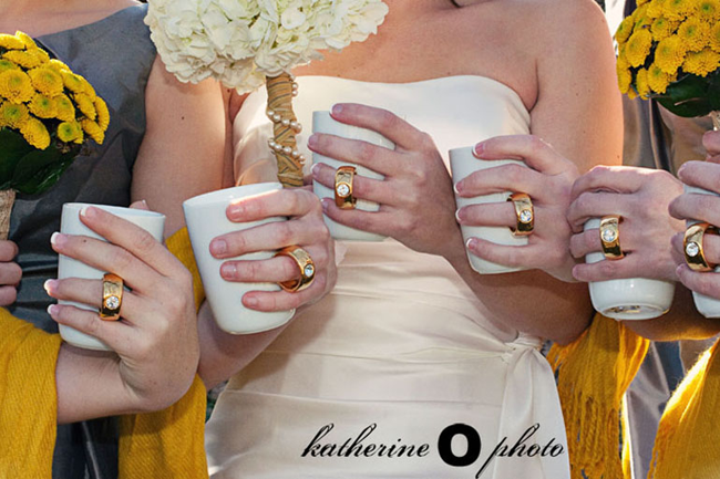 Bridemaids wearing grey dresses with yellow pashmina and yellow bouquet of mums. Bride in white strapless gown holding a bouquet of white hydrangeas with twine and pearls around stem all holding white coffee mug with gold diamond rings attached as the mug handle