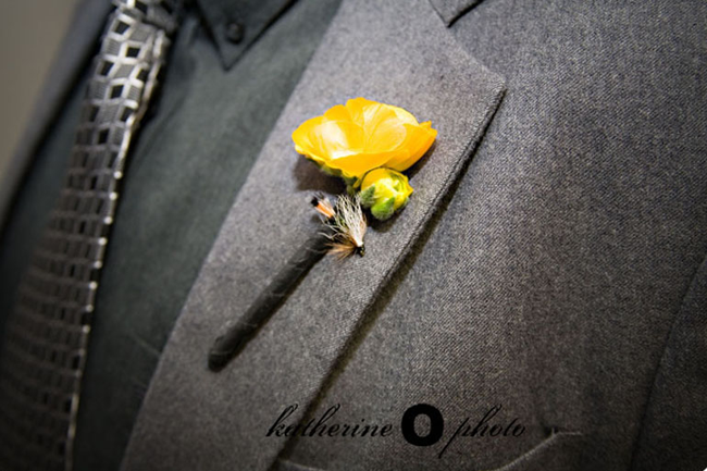 Groom in grey suit and shirt with light and dark grey square pattern tie. Small yellow flower boutonniere