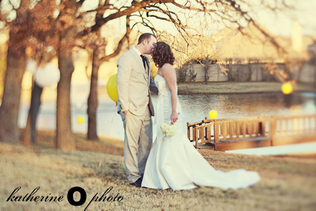 bride wearing white strapless mermaid gown and groom wearing grey suit with black tie standing in forest with yellow balloon kissing. bridge and river in the background.