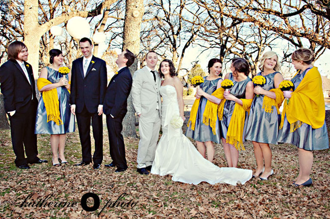 5 Bridemaids wearing grey dresses with yellow pashmina and holding yellow bouquet of mums. Bride in white strapless gown holding a bouquet of white hydrangeas. 3 grooms men wearing black suits and yellow boutonniere. Groom wearing black tie and grey suit. All standing in the forest with white lantern hanging from trees.