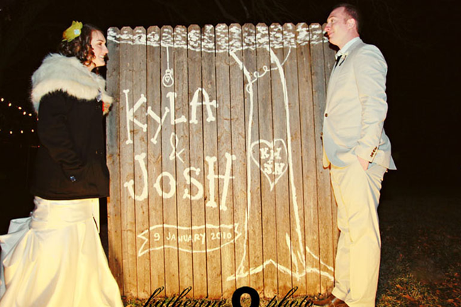 Bride wearing white mermaid dress, black jacket and white fur stole and groom wearing grey suit with black tie standing infront of fence that had white painted tree with bride and grooms initials and their names spelled out and date they got married