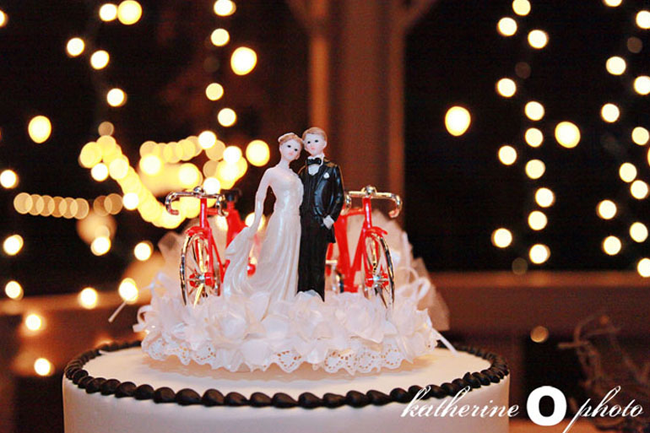 White cake with black pipping and a bride and groom cake topper with vintage red bikes.