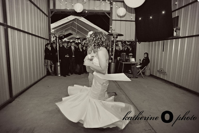 Bride in white strapless mermaid dress with groom dancing in middle of barn with white lanterns and small white light and guests watching in the back grounds hanging from ceiling.
