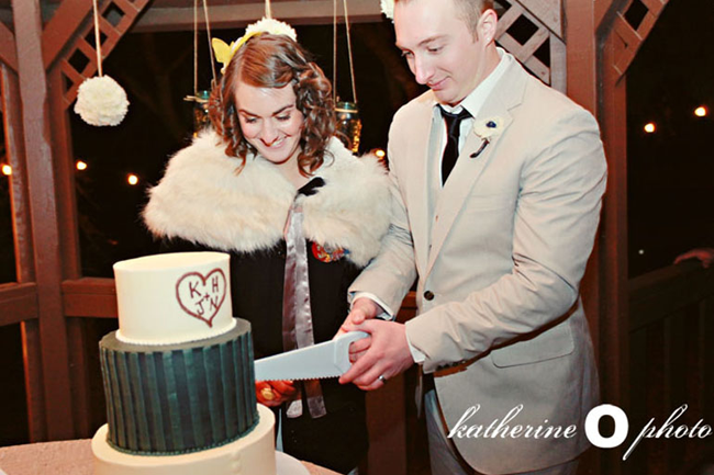 bride wearing white fur stole and groom wearing grey suit and black tie cutting black and white cake with a red heart and bride and grooms initials.
