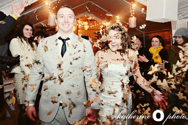 Bride wearing white strapless mermaid dress and groom wearing grey suit and black tie and making their grand exit. Guests throwing dried leaves at them