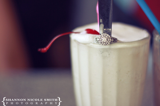 Round diamond engagement ring with halo around spoon that is in a milkshake