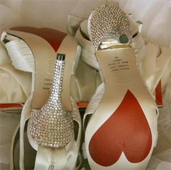 White bridal pumps with rhinestone crystals on heel and red heart on sole