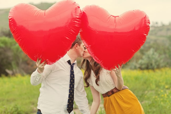 couple hold large red heart balloons