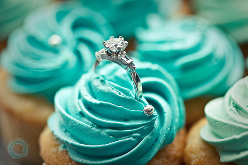 White engagement ring with round diamond and 2 baguettes in blue icing on a vanilla cup cake