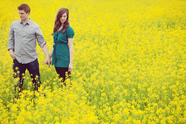 Engaged Couple holding hands taking photos in a field of yellow mustard flower engagement shoot