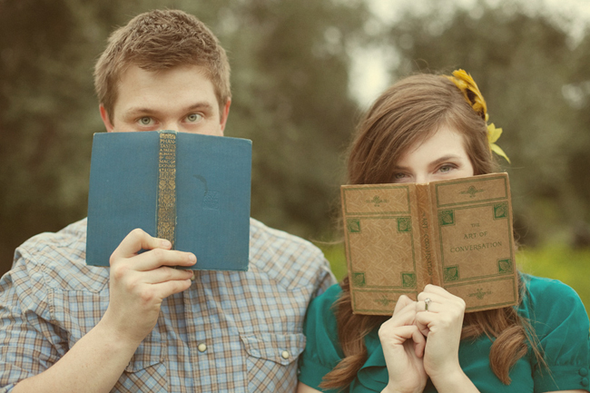 Engaged couple standing outside holding vintage books above their mouth. Girl wearing teal shirt with yellow feather hair accessory