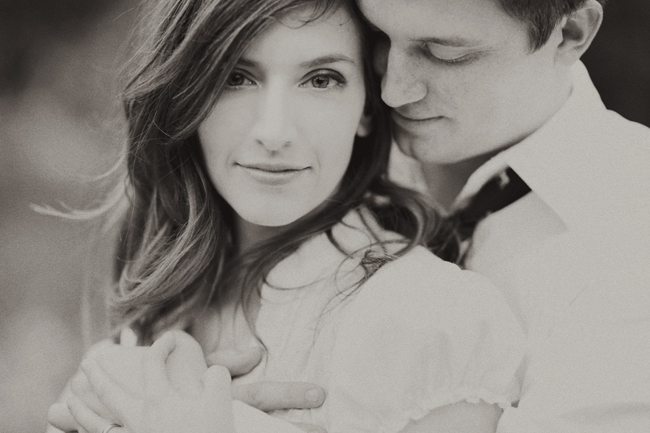 Black and white photo of engaged couple with guy wrapping his hands around his fiancee and girl looking at the camera