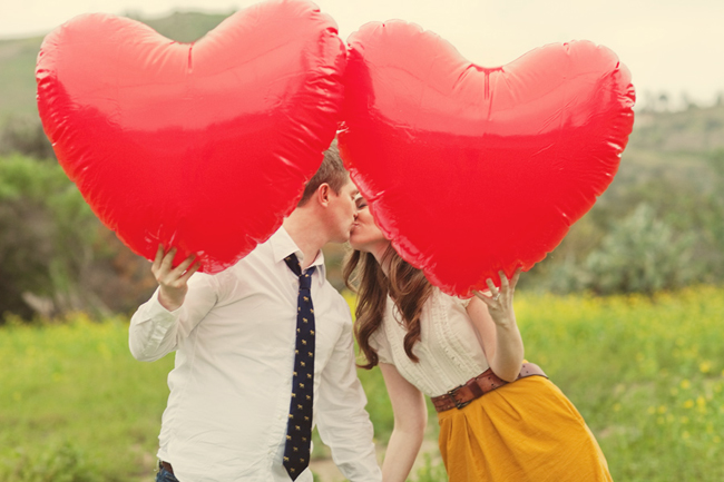 Engagaed couple in field of mustard flowers hold 2 large red heart balloons