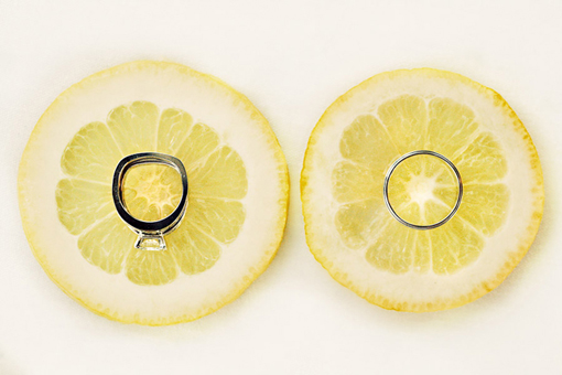 White gold engagement ring and wedding band sitting on 2 pieces of lemon