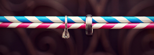 White gold engagement ring and wedding band on a 2 straws that are white, pink and blue stripped straws