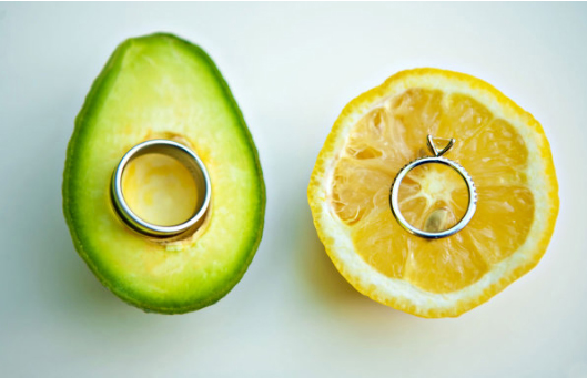White gold men's wedding band on a piece of avocado and princess cut engagement ring on a piece of lemon