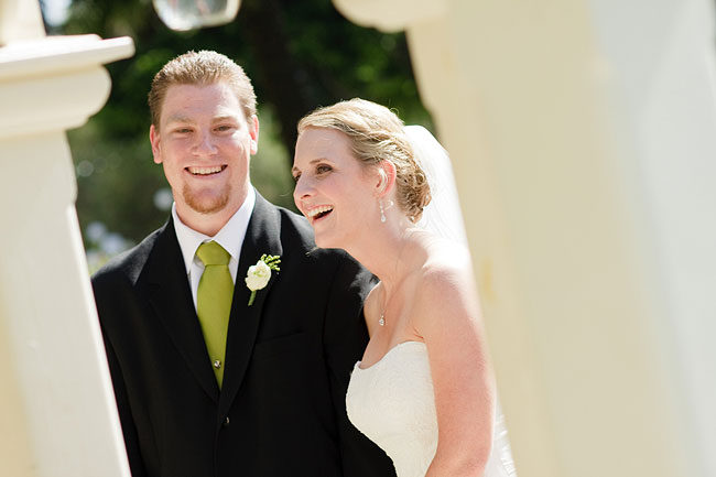Groom in lime green necktie smiles with bride