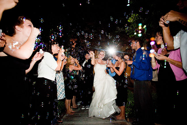 bride and groom exit as guests blow bubbles