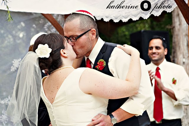 bride and groom sharing first kiss under chuppah