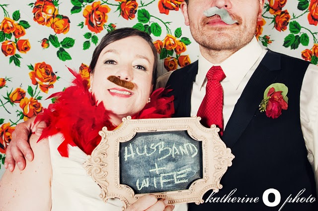 "photobooth shot of bride and groom announcing ""husband and wife"""