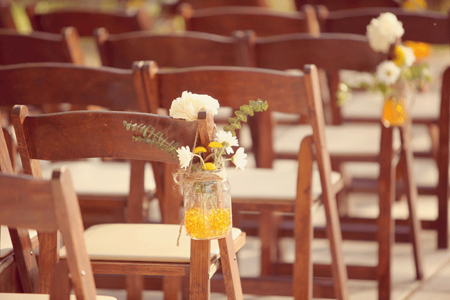 jars with flowers hang from wooden foldup chairs at wedding ceremony at Umluaf Sculpture Garden
