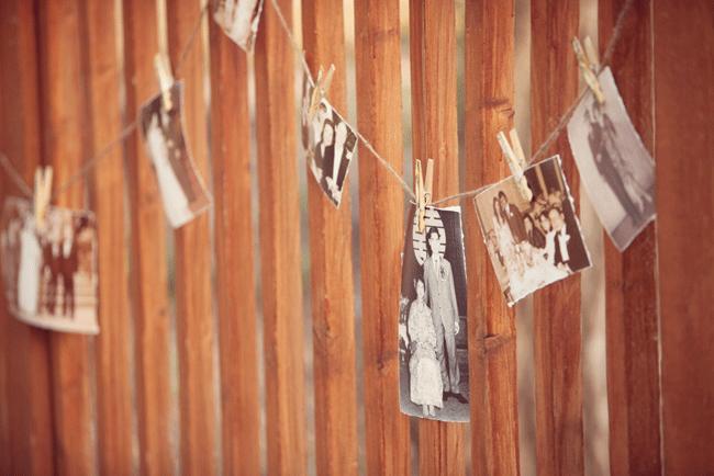 old photos hang from pinclothes at wedding at Umluaf Sculpture Garden