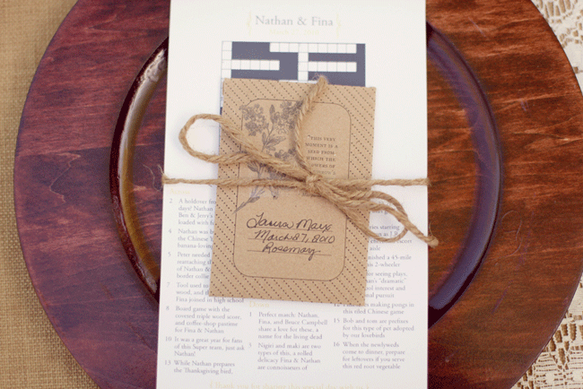 wedding menu and crossword puzzle tied together with twine ontop of wood charger