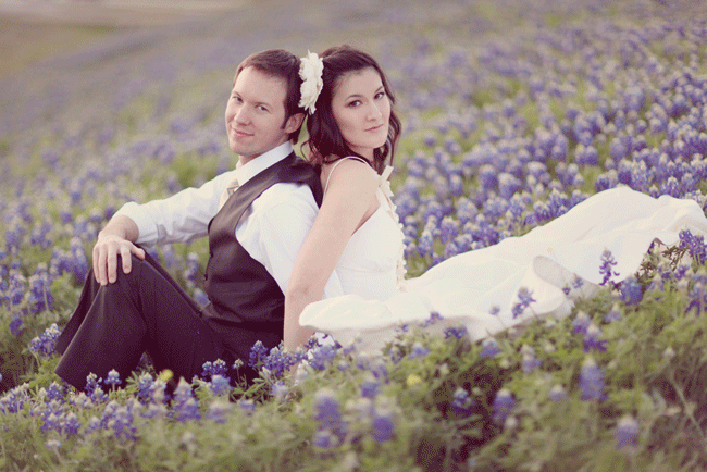 bride and groom sitting back-to-back in field of purple flowers